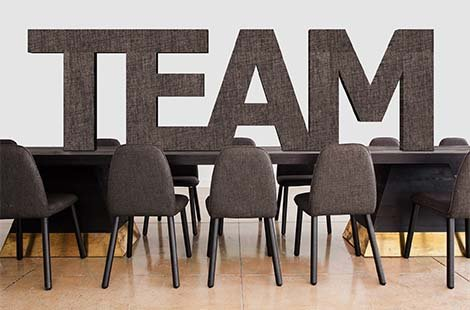 team written in capital letters position on a large table surrounded by chairs
